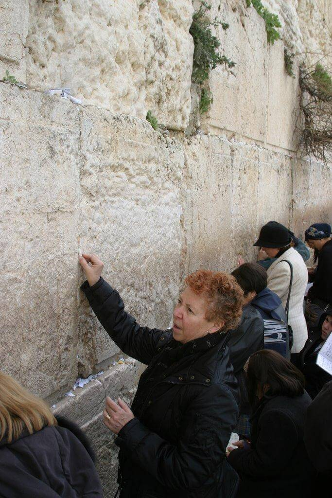 Johanna McGeary, TIME Bureau Chief, slips a note into the cracks of the Western Wall